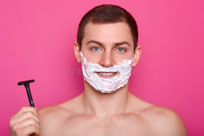 Il giovane osservato blu bello con capelli scuri, radenti il gel, tiene il rasoio tagliente, ha ente muscolare, esamina direttame fotografia stock