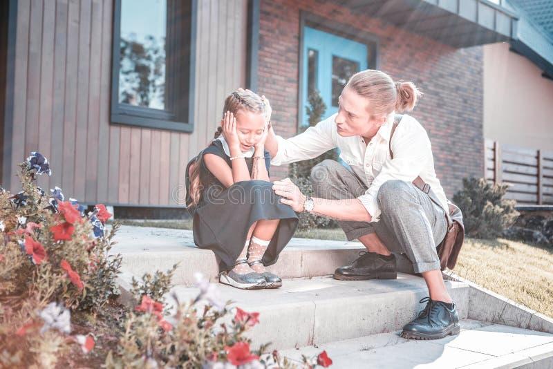 Il giovane padre amoroso che calma sua figlia emozionale che ritiene molto si è preoccupato immagine stock libera da diritti