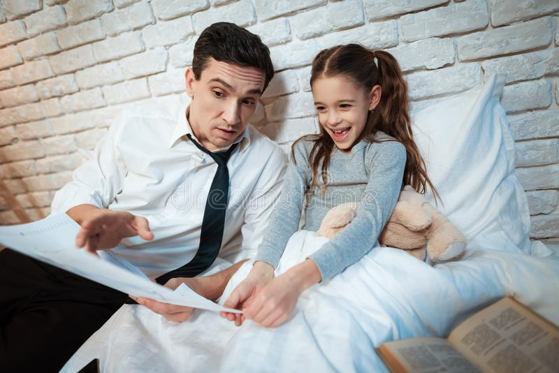 Il giovane padre dice sua figlia circa il suo lavoro L'uomo d'affari mostra la piccola figlia lui fa immagine stock