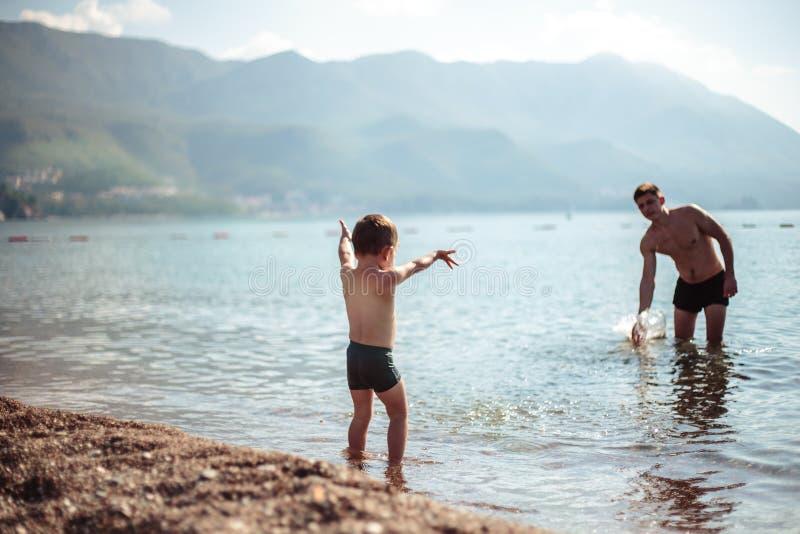 Il Giovane Padre E Il Figlio Giocano Insieme In Acqua..