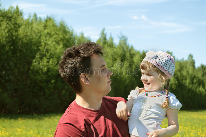 Il giovane padre esamina la piccola figlia felice fotografie stock