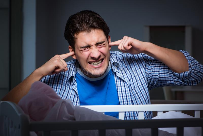 Il giovane padre nell'ambito dello sforzo dovuto il bambino che grida alla notte immagini stock libere da diritti