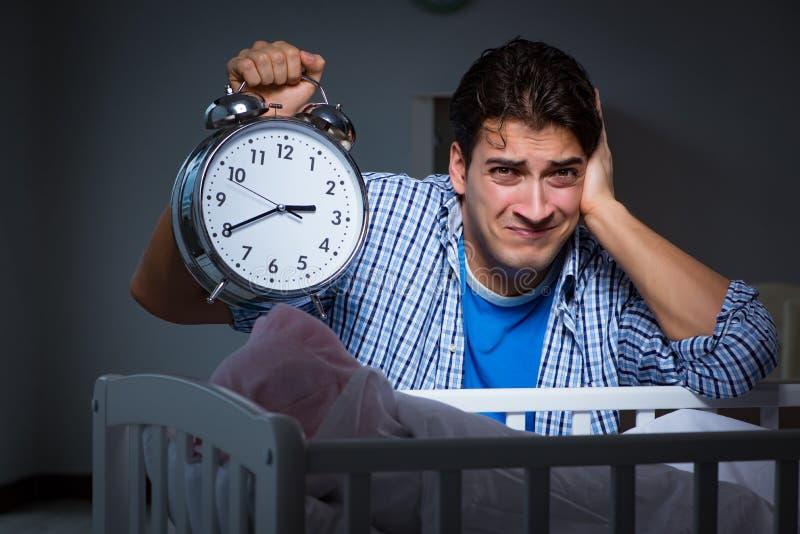 Il giovane padre nell'ambito dello sforzo dovuto il bambino che grida alla notte fotografia stock