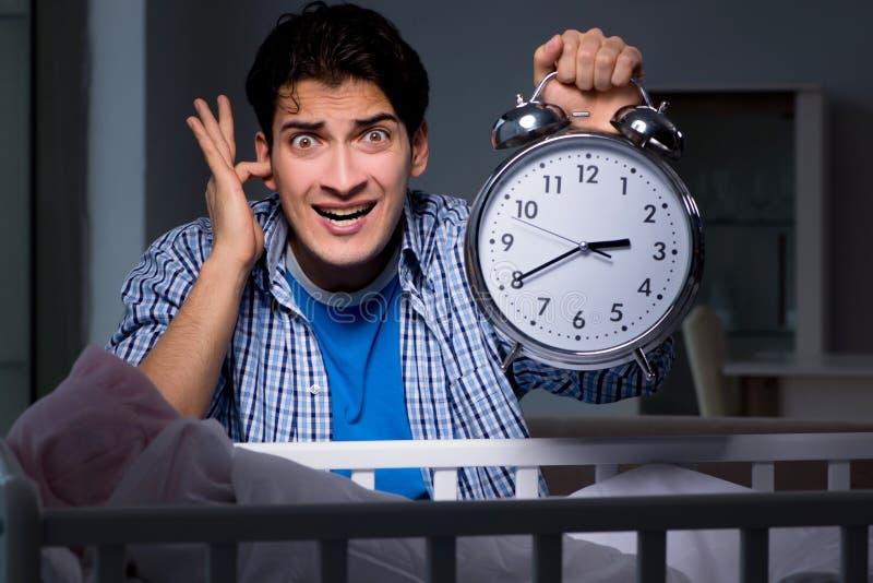 Il giovane padre nell'ambito dello sforzo dovuto il bambino che grida alla notte immagine stock libera da diritti