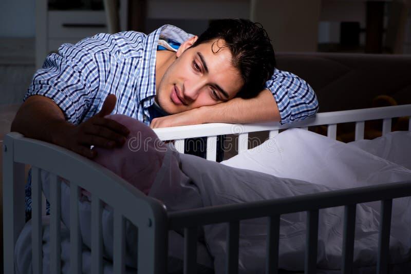 Il giovane papà del padre che dorme mentre occupandosi del neonato fotografie stock
