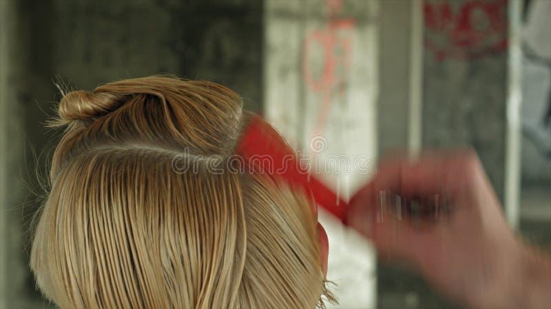 Il giovane parrucchiere della donna di modo fa l'acconciatura per una ragazza fotografie stock