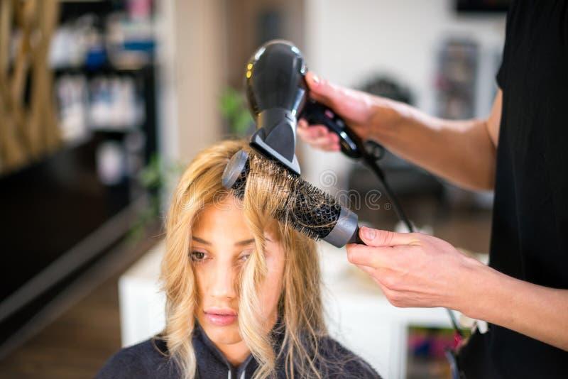 Il giovane parrucchiere maschio è capelli di secchezza della giovane donna fotografia stock