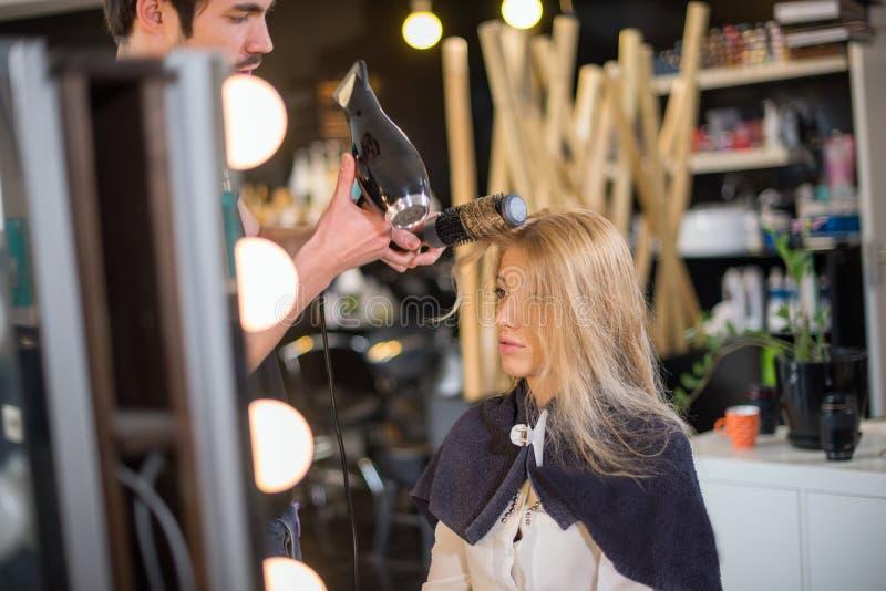 Il giovane parrucchiere maschio sta asciugando i capelli delle ragazze fotografia stock libera da diritti