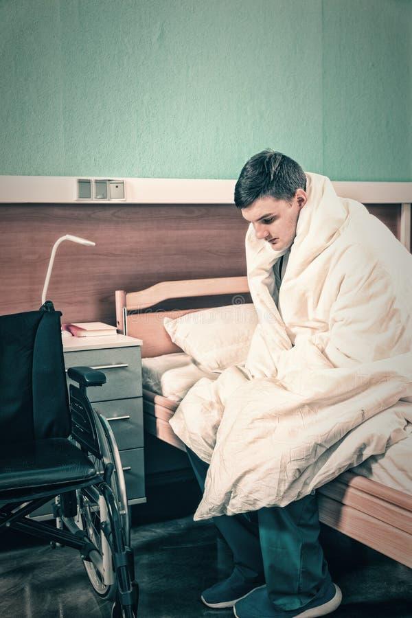 Il giovane paziente malato maschio triste che si siede sul letto di ospedale ha riguardato w immagini stock libere da diritti