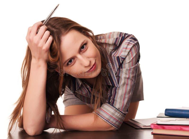 Il giovane pensiero dell'insegnante si è appoggiato a sullo scrittorio immagini stock libere da diritti