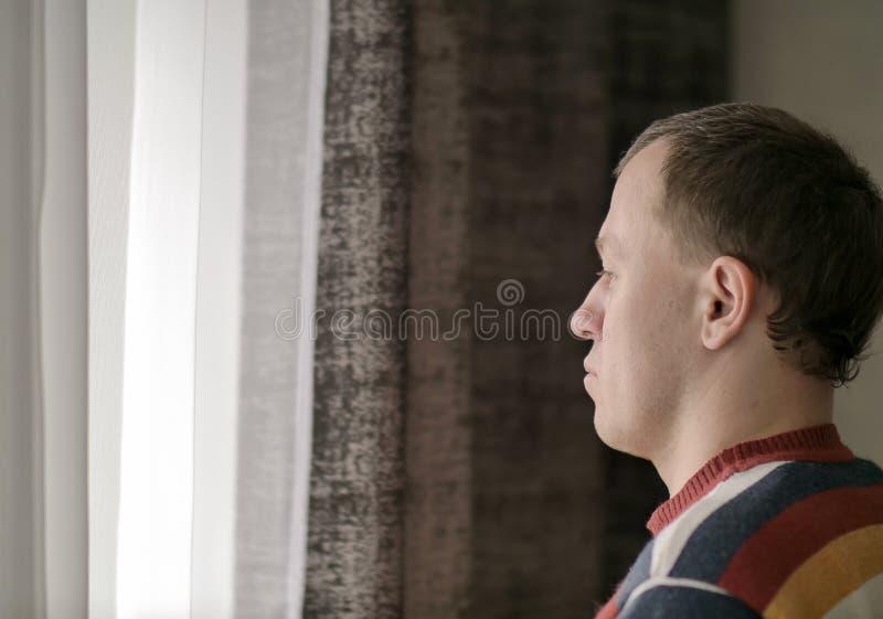 Il giovane pensieroso guarda fuori la finestra fotografia stock