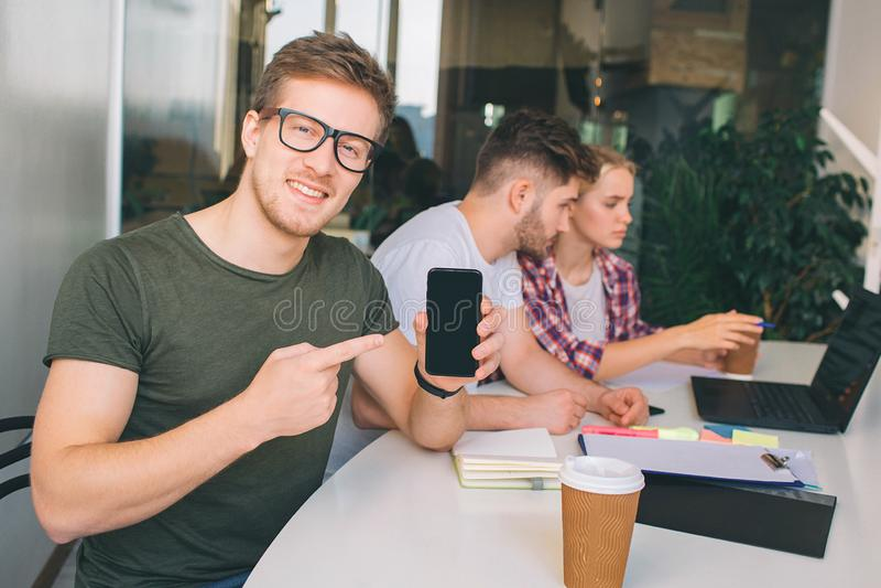 Il giovane piacevole in vetri indica sul hpone in mani Considera la macchina fotografica Altri due giovani lavorano insieme ad un immagine stock