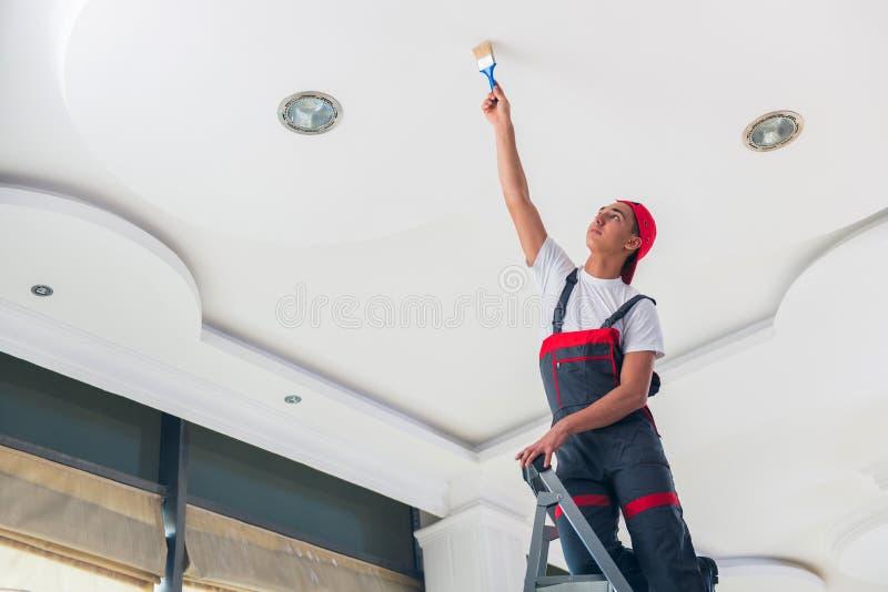 Il giovane pittore che dipinge il soffitto nel concetto della costruzione fotografie stock libere da diritti