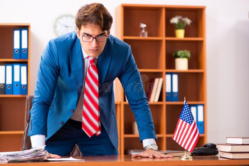 Il giovane politico bello che si siede nell'ufficio fotografia stock