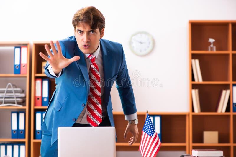 Il giovane politico bello che si siede nell'ufficio immagini stock