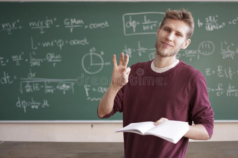 Il giovane pollice dell'insegnante maschio di corso online di fisica sull'aula con la lavagna con le formule copia lo spazio immagine stock