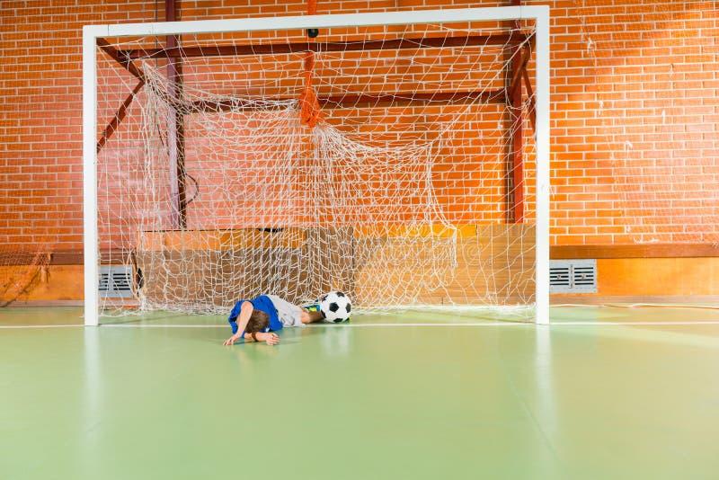 Il giovane portiere ha mancato il pallone da calcio immagine stock