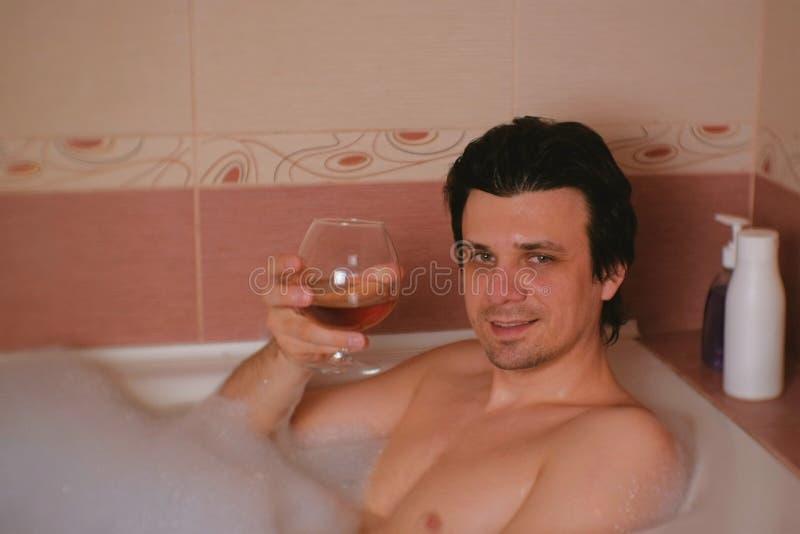 Download Il Giovane Prende Un Bagno Con Schiuma Ed Andando Beve Il Whiskey Sorridendo Ed Esaminando Macchina Fotografica Immagine Stock - Immagine di sguardo, sano: 117981781