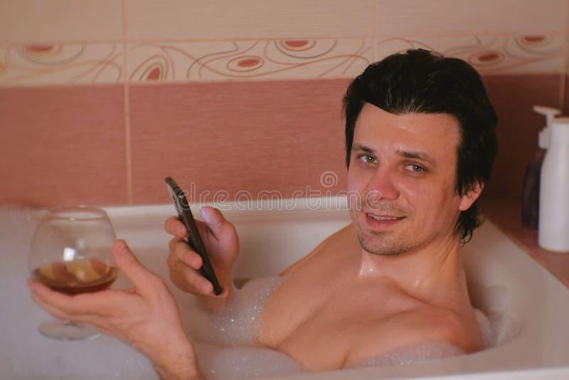 Download Il Giovane Prende Un Bagno Con Schiuma, Passante In Rassegna Internet Sul Telefono Cellulare, Le Bevande Whiskey Ed I Sorrisi Che Fotografia Stock - Immagine di bathroom, sano: 117981810