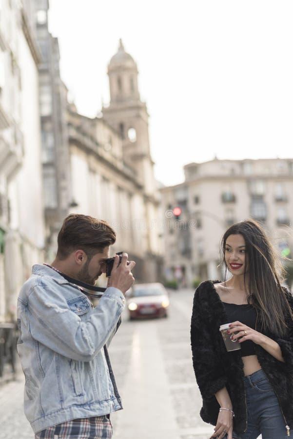 Il giovane prende un'immagine del suo grilfriend nell'immagine della città di aria aperta fotografie stock libere da diritti