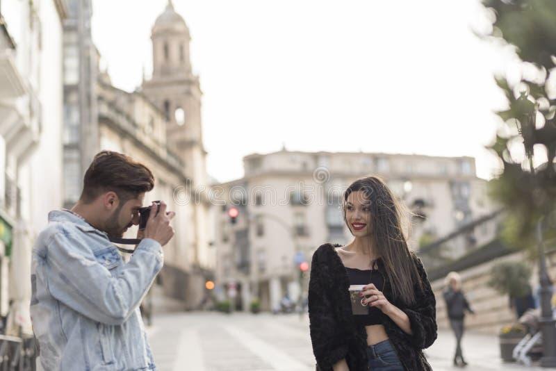 Il giovane prende un'immagine del suo grilfriend nell'immagine della città di aria aperta immagini stock libere da diritti