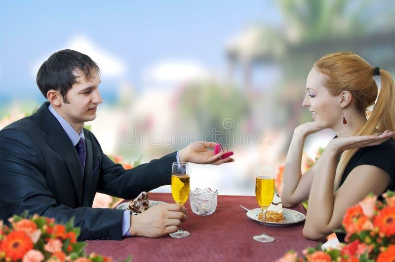 Il giovane propone l'unione alla donna in ristorante. fotografie stock