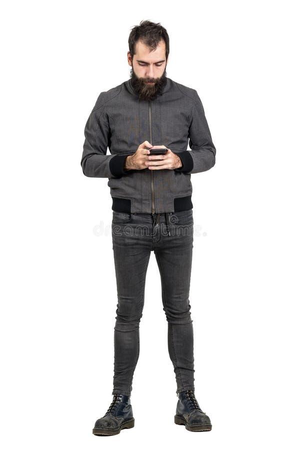 Il giovane punker barbuto che indossa l'esercito anziano inizializza il messaggio di battitura a macchina sul suo telefono cellul fotografie stock