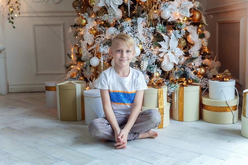 Il giovane ragazzo apre un regalo sotto un albero di Natale immagini stock