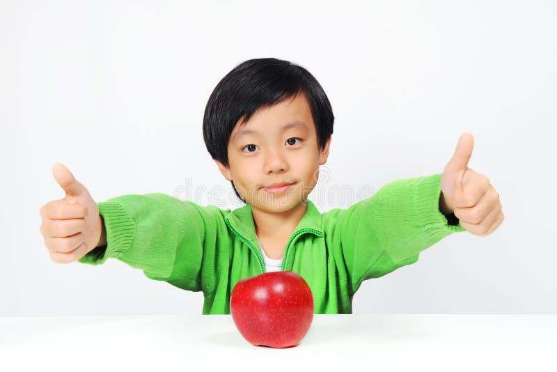 Il giovane ragazzo asiatico dà i pollici in su per alimento sano fotografie stock libere da diritti