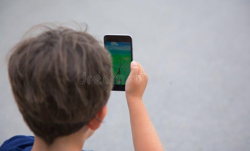 Il giovane ragazzo che gioca Pokemon va immagine stock libera da diritti