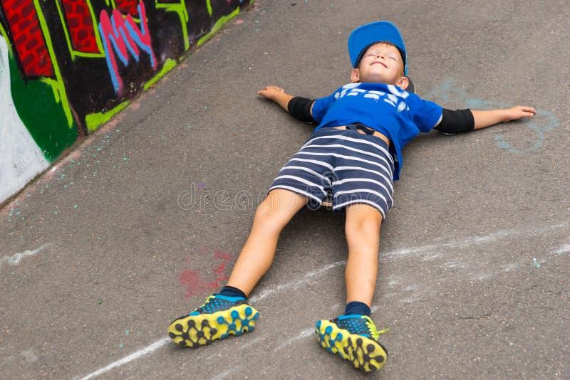 Il giovane ragazzo che si trova sopra appoggia nel lotto vicino alla parete dei graffiti fotografia stock