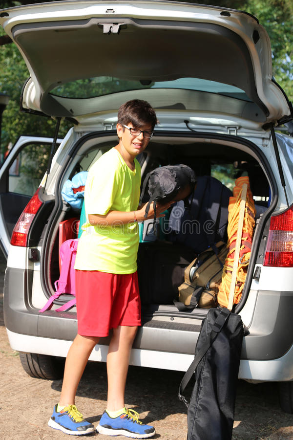 Il giovane ragazzo con i vetri carica i bagagli fotografia stock libera da diritti