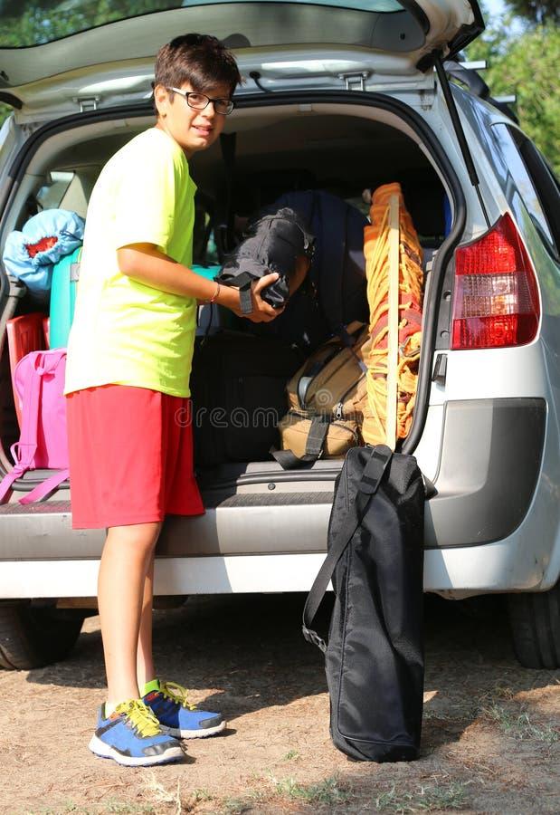 Il giovane ragazzo con i vetri carica i bagagli nel tronco dell'automobile immagini stock