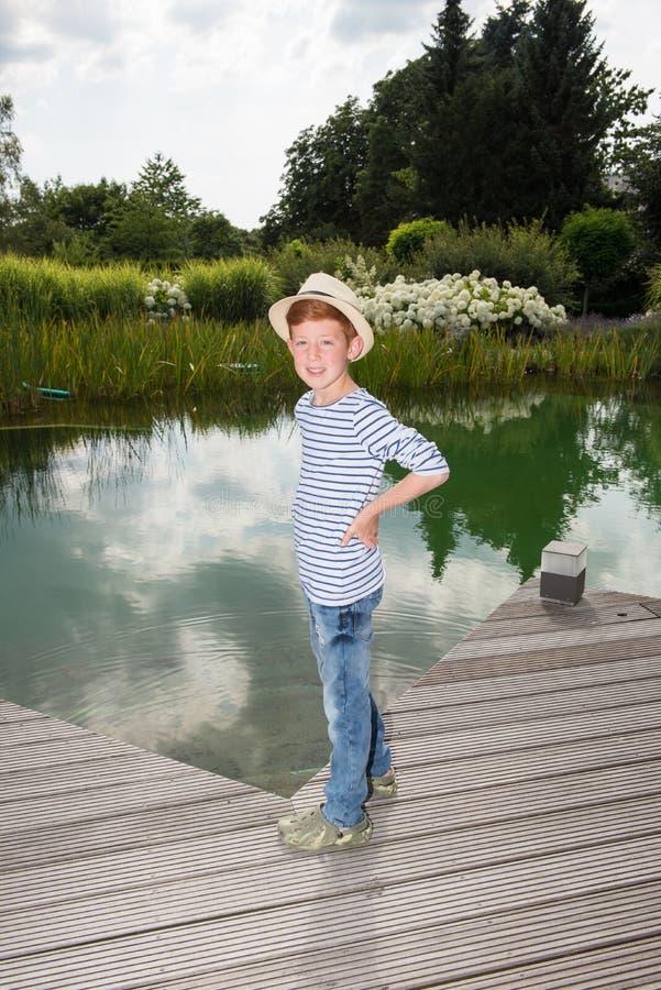 Il giovane ragazzo con il cappello sta sorridendo nella macchina fotografica fotografia stock