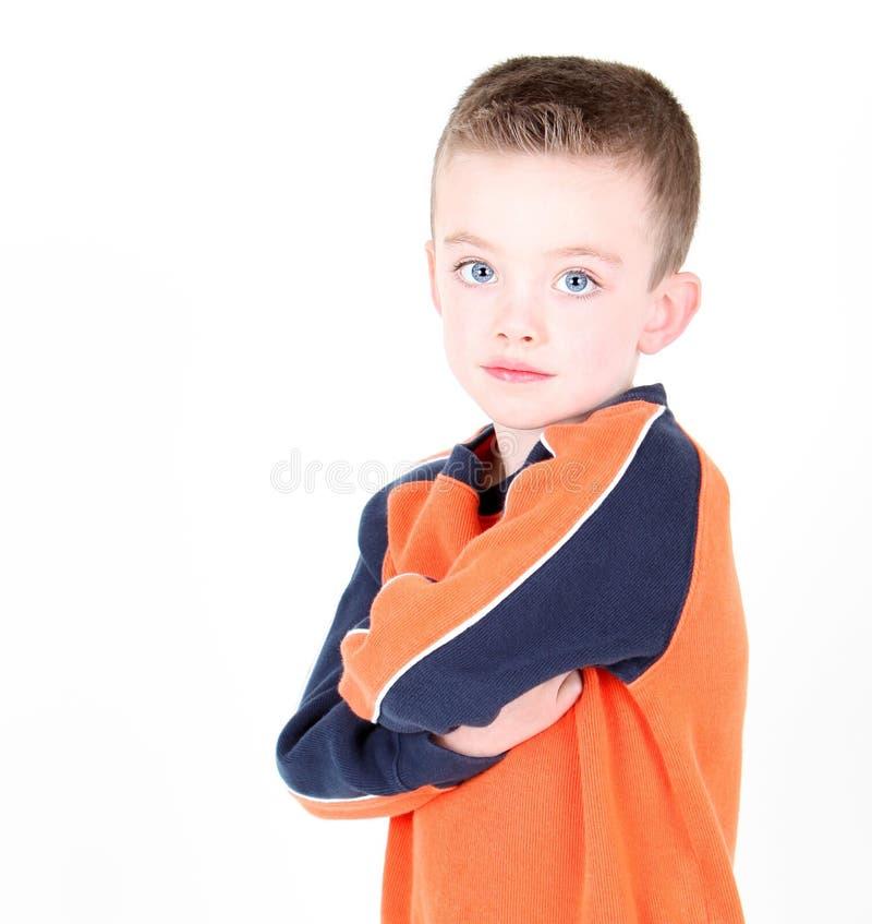 Il giovane ragazzo con le braccia ha attraversato isolato immagine stock