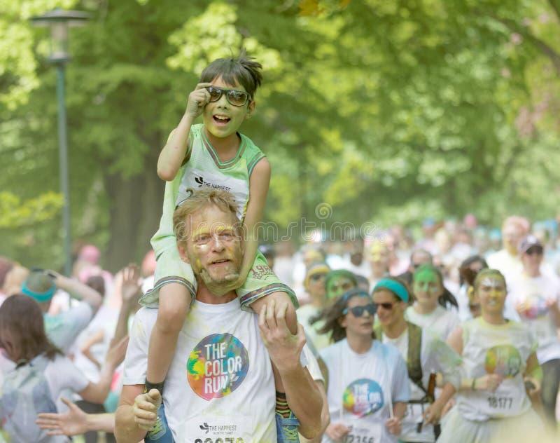 Il giovane ragazzo con pittura verde nel suo fronte sui suoi padri mette fotografie stock libere da diritti