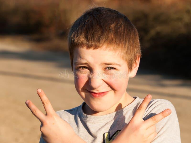 Il giovane ragazzo fa il gesto della vittoria immagine stock libera da diritti