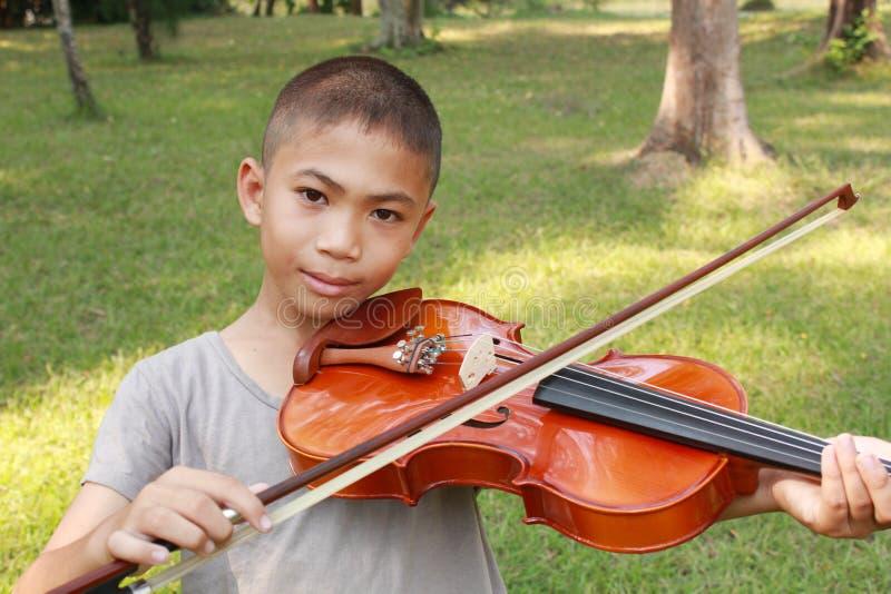 Il giovane ragazzo felice gioca il suo violino fotografie stock libere da diritti