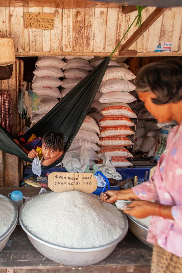 Il giovane ragazzo khmer si trova in un'amaca che aspetta per vendere i risi a grani lunghi al mercato locale Dong Tong Market, K immagini stock libere da diritti