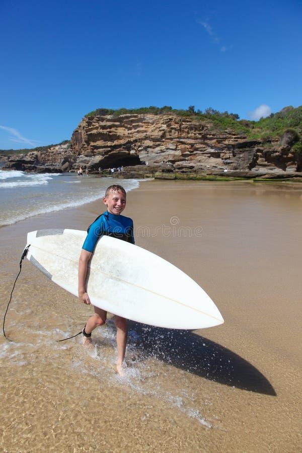 Il giovane ragazzo lascia il trasporto della spuma è surf immagine stock