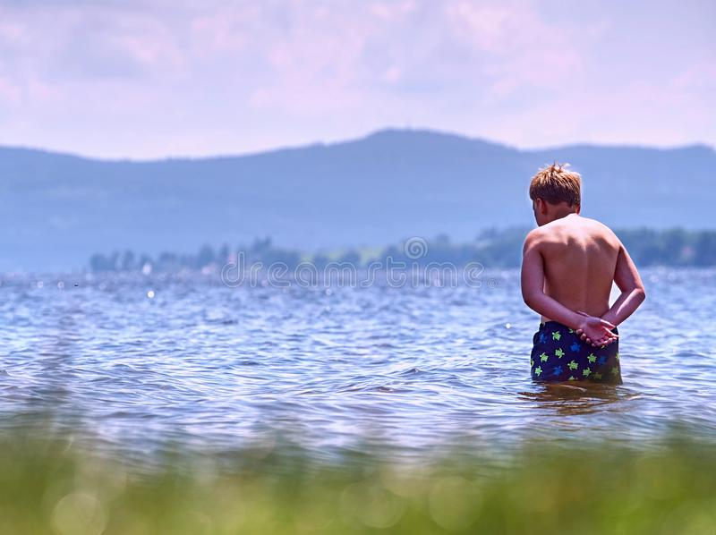 Il giovane ragazzo nel nuoto blu mette il soggiorno in cortocircuito in acqua fredda del lago fotografia stock libera da diritti