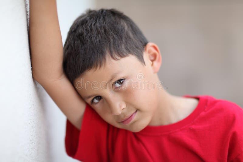 Il giovane ragazzo pende contro la parete immagini stock libere da diritti