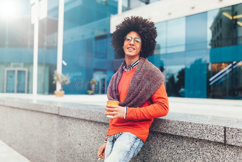 Il giovane ragazzo razza mista riccio beve il caffè sulla via contro lo sfondo degli edifici per uffici immagini stock