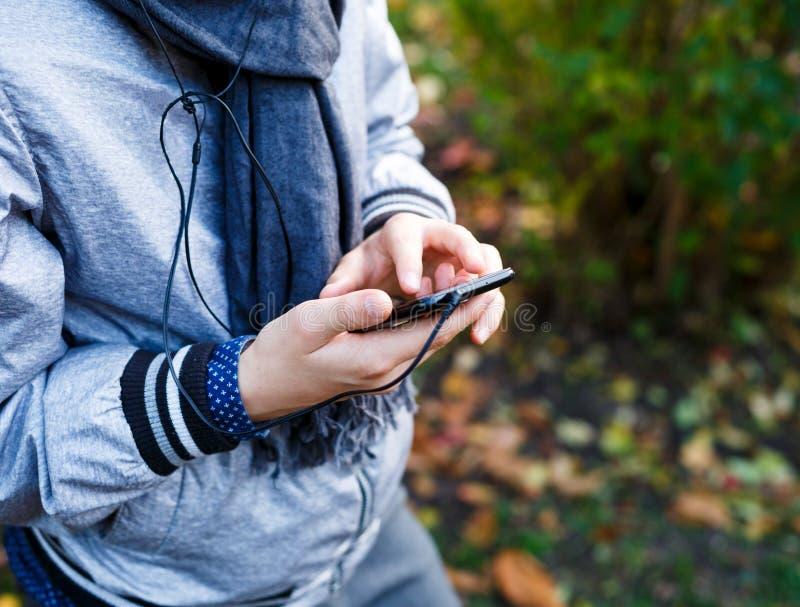 Il giovane ragazzo in rivestimento grigio con la sciarpa grigia tiene ed utilizza lo smartphone con le cuffie esterne sopra il fo fotografia stock