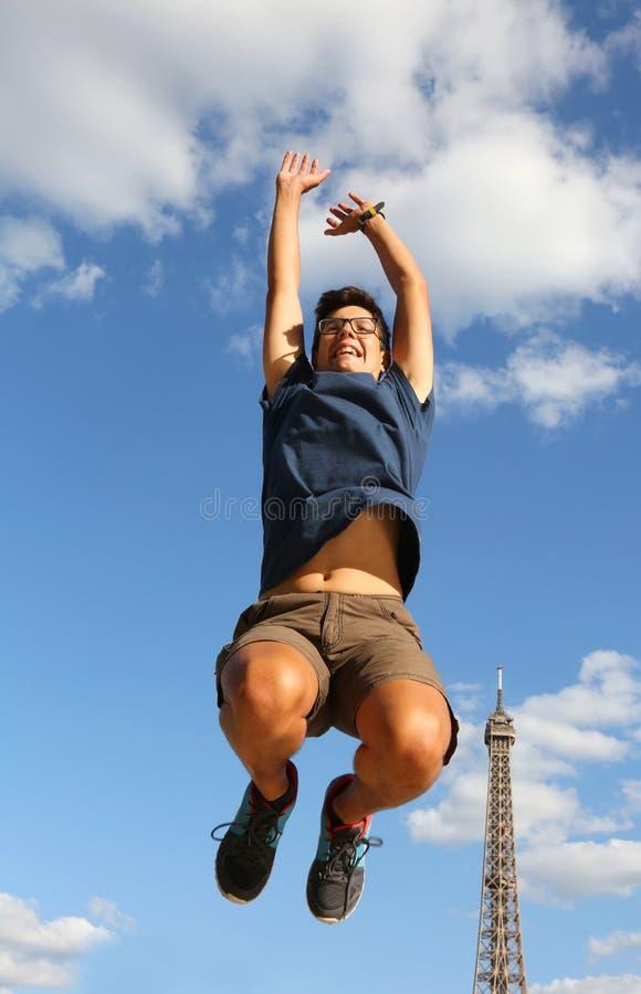 Il giovane ragazzo salta con la torre Eiffel su fondo fotografia stock libera da diritti