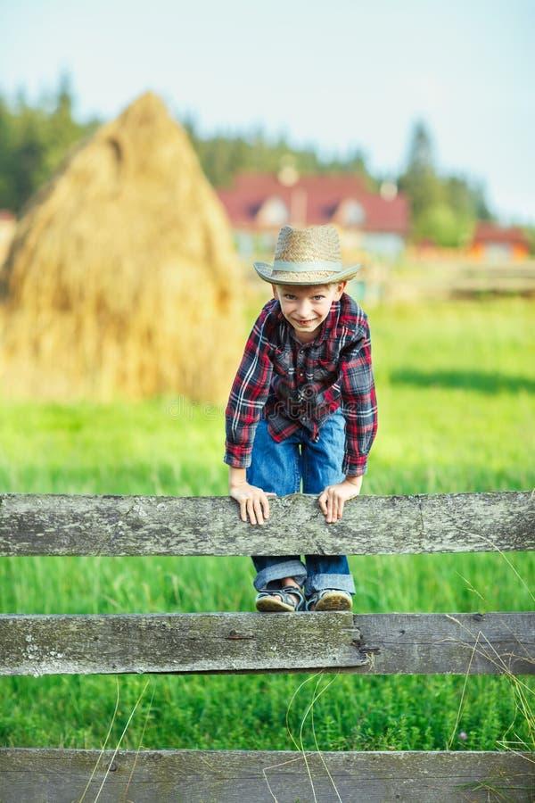 Il giovane ragazzo scavalca lo sguardo di legno del recinto diritto, vicino su fotografia stock