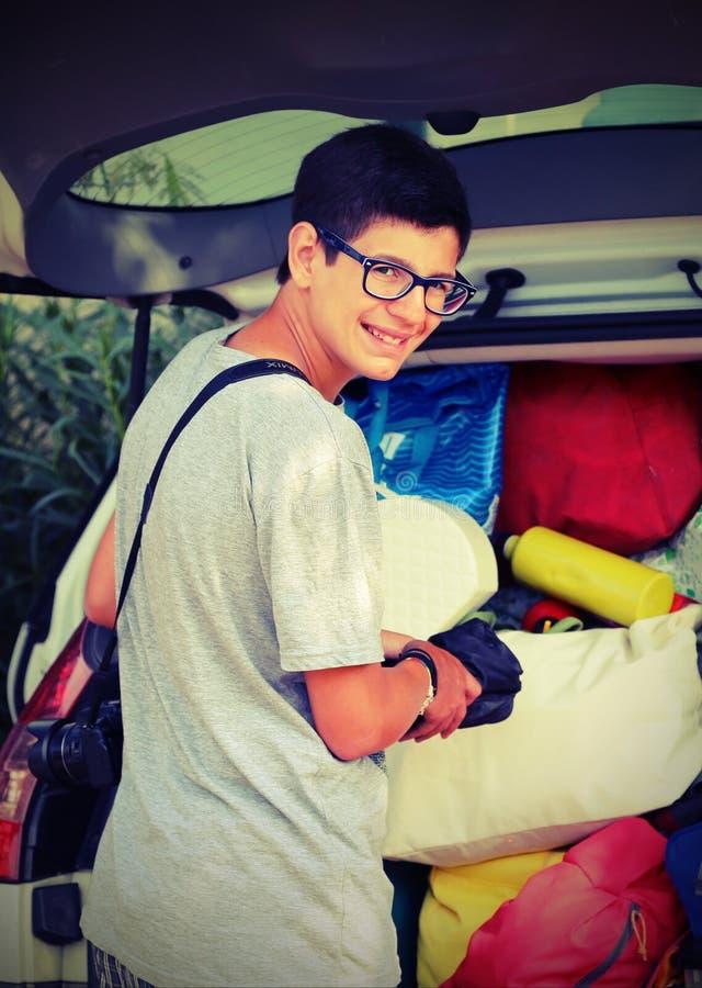 Il giovane ragazzo sorridente con i vetri mette le valigie nello spirito dei bagagli immagini stock libere da diritti