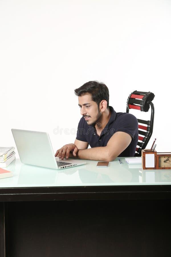 Il giovane ragazzo sta utilizzando il computer portatile immagine stock