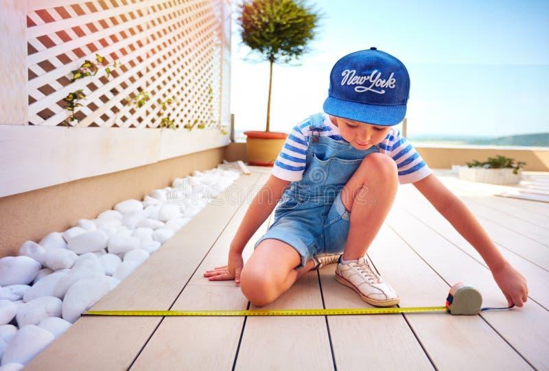Il giovane ragazzo sveglio, bambino aiuta il padre con il rinnovamento della zona del patio del tetto immagine stock