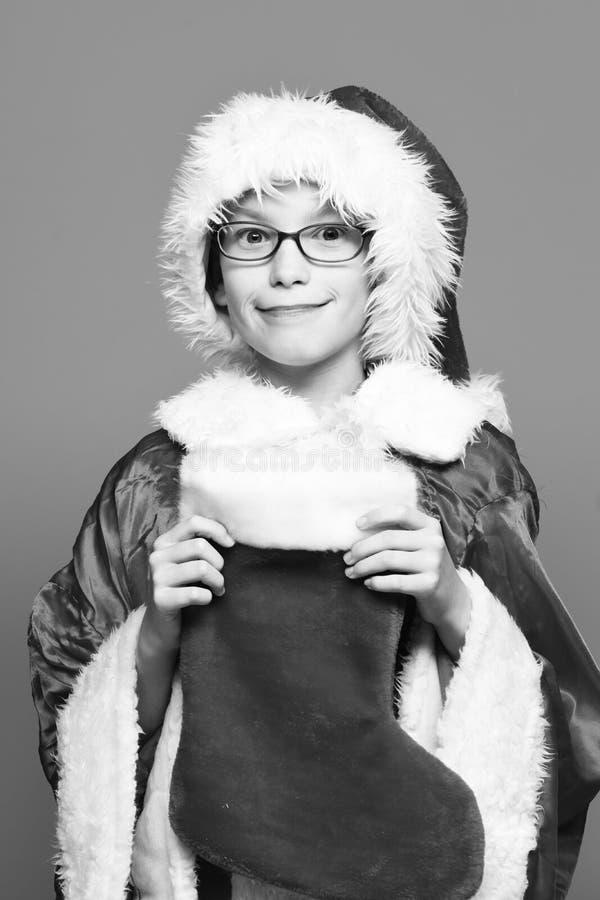 Il giovane ragazzo sveglio del Babbo Natale con i vetri in cappello rosso del nuovo anno e del maglione giudica il natale o il na fotografie stock libere da diritti